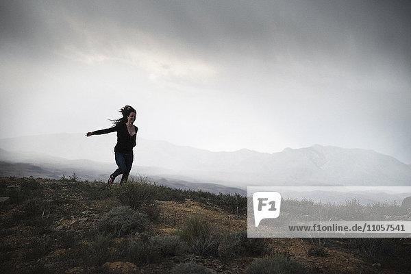 Frau rennt in einer Prärie unter bewölktem Himmel.
