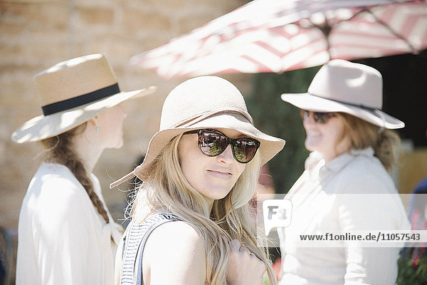 Portrait of three women wearing hats and sunglasses.