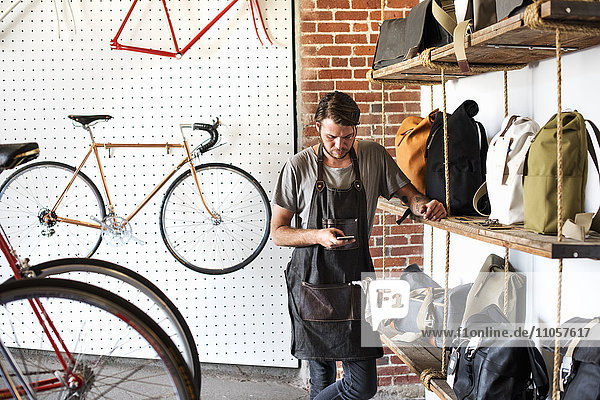 A man working in a bicycle repair shop looking at his smart phone.