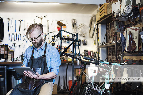 A man working in a bicycle repair shop  seated using a digital tablet.