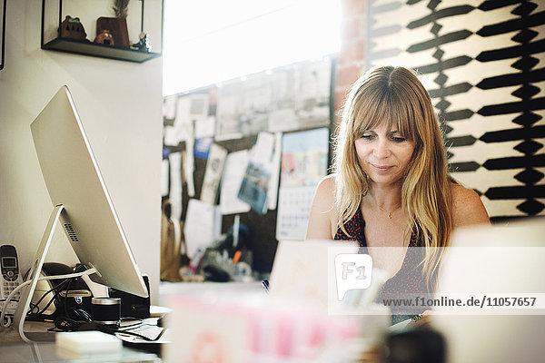 Frau  die in einem Büro an einem Schreibtisch mit einem Computer sitzt und arbeitet.