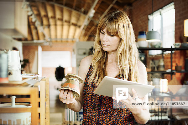 Frau in einem Geschäft  die ein digitales Tablett und einen kleinen Keramiktopf in der Hand hält.