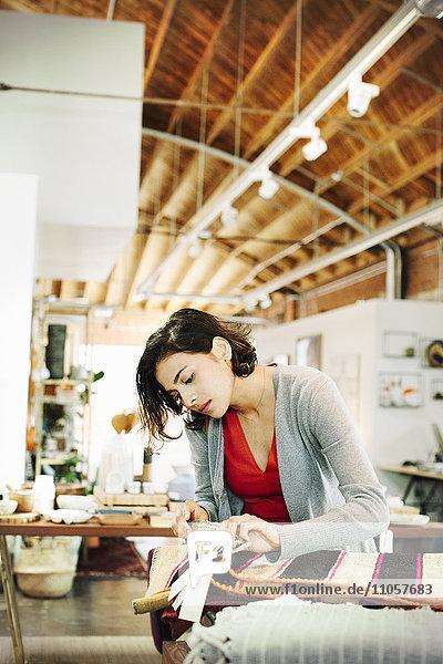Junge Frau in einem Geschäft  die sich kleine gestreifte Teppiche ansieht.