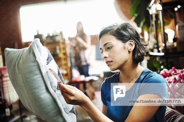 Frau steht in einem Geschäft  hält ein Kissen in der Hand und liest das Preisschild.