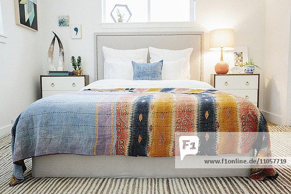 Ein Schlafzimmer in einer Wohnung mit einem Doppelbett und neben Schränken und einer lebhaft gestreiften Tagesdecke.