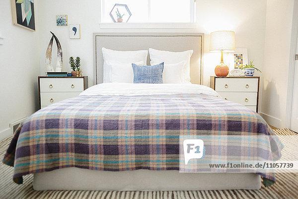 Ein Schlafzimmer in einem Appartement  Doppelbett mit einem karierten violetten und cremefarbenen Bettbezug