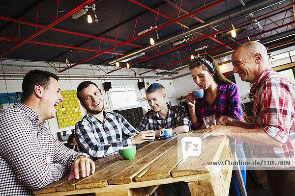 Spezialisiertes Kaffeehaus. Fünf Personen  die um einen Holztisch sitzen.
