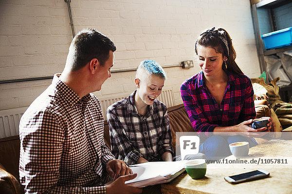 Spezialisiertes Kaffeehaus. Drei Personen  zwei Erwachsene und ein Jugendlicher auf einem Sofa sitzend.