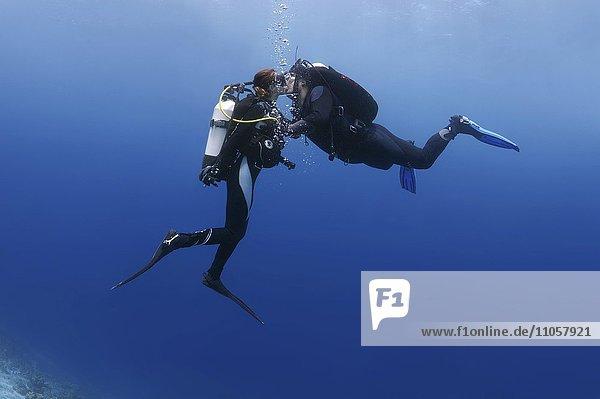 Junges Paar,  Taucher küssen sich unter Wasser,  Indischer Ozean,  Malediven,  Asien