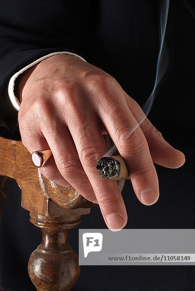 Hand mit Siegelring und Zigarre auf Armlehne