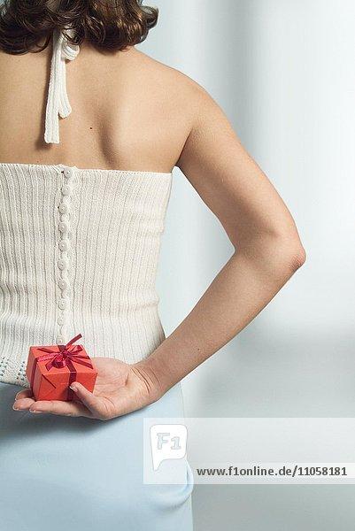 Frau versteckt Geschenk hinter ihrem Rücken