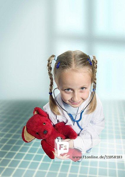 Mädchen hört mit Stethoskop ihren Teddy ab  Symbolbild Berufswunsch Ärztin