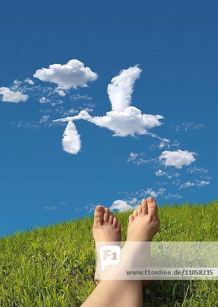 Frau liegt auf Wiese  Detail Füße  Himmel  Wolkenformation in Form eines Storches  der ein Baby in einer Windel bringt