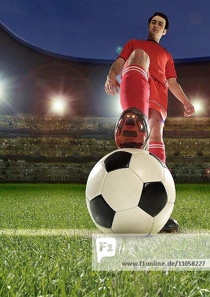 Fußballspieler hält Fuß auf Fußball  Fußballstadion