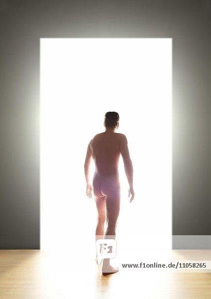 Nackter junger Mann  Rückenansicht  geht durch eine Tür ins Licht