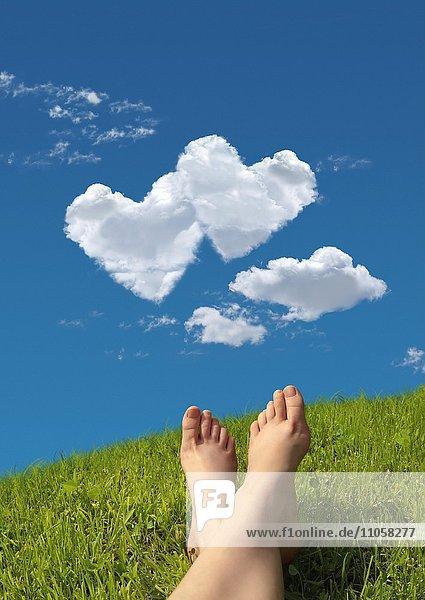 Frau liegt auf Wiese  Detail Füße  Himmel  Wolkenformation in Herzform