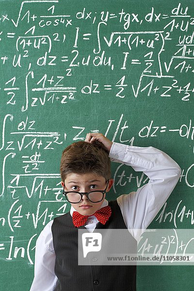Ratloser Schuljunge mit Brille und Fliege vor Schultafel mit mathematischen Gleichungen