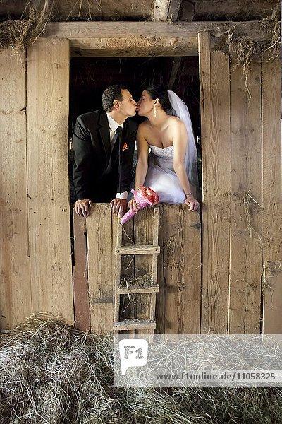 Brautpaar küsst sich im Heustadel