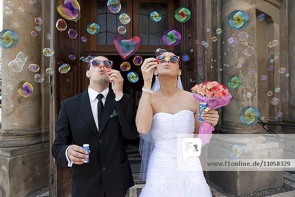 Brautpaar macht Seifenblasen  vor der Marienkirche  Krakau  Polen  Europa