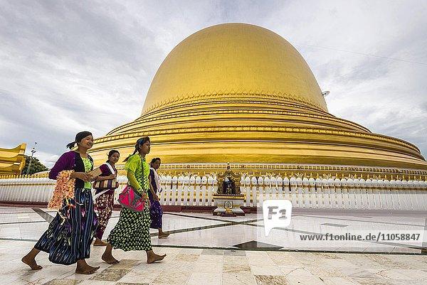 Girls walk in front of Kaunghmudaw pagoda or Yaza Mani Sula Kaunghmudaw or Rajamanicula  Sagaing Region  Myanmar  Burma  Asia