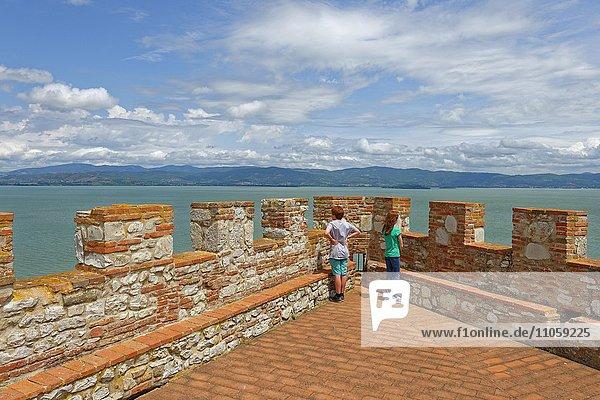 Two children stand on battlements  Fortezza  Rocca del Leone  Castiglione del Lago  on Lake Trasimeno  Lago Trasimeno  Umbria  Italy  Europe