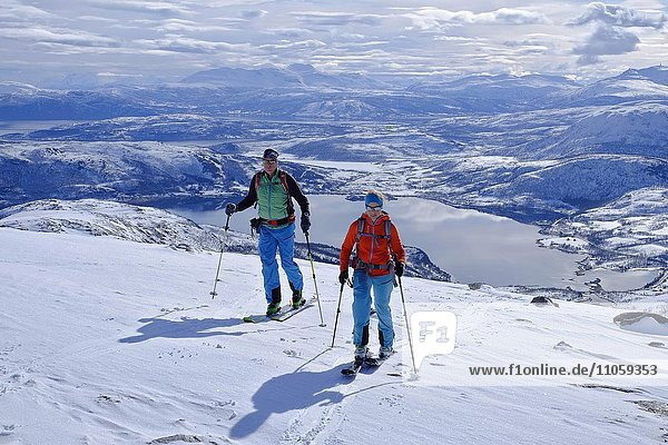 Zwei Skitourengeher im Aufstieg zum Skarelvfjellet  Verschneite Berglandschaft mit Seen  Senja  Norwegen  Europa