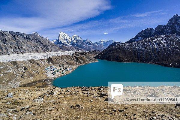 Ausblick auf den See und das Dorf Gokyo von Gokyo Ri aus  der Ngozumba Gletscher und schneebedeckte Berge in der Ferne  Gokyo  Solo Khumbu  Nepal  Asien
