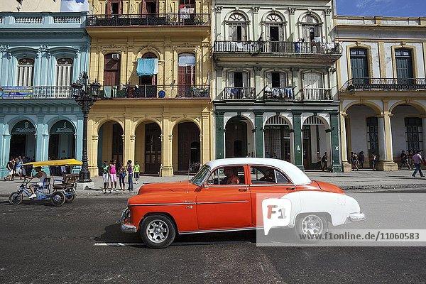Straßenszene  Oldtimer  orange-weiß  vor bunten Hausfassaden am Prado  Altstadt  Havanna  Kuba  Nordamerika