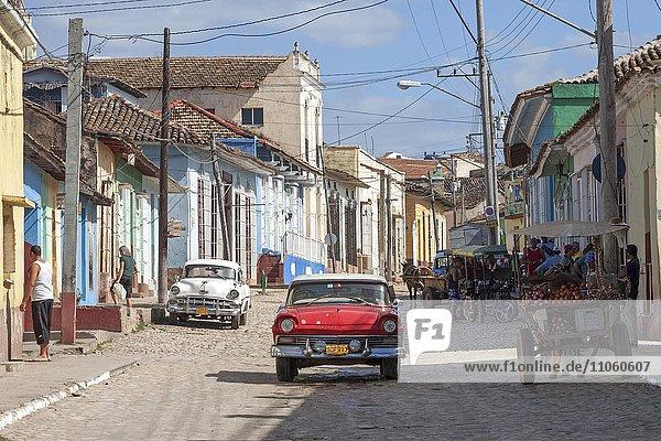 Straßenszene  typische Straße mit Kopfsteinpflaster  bunte Häuser und Oldtimer  historische Altstadt  Trinidad  Provinz Sancti Spiritus  Kuba  Nordamerika