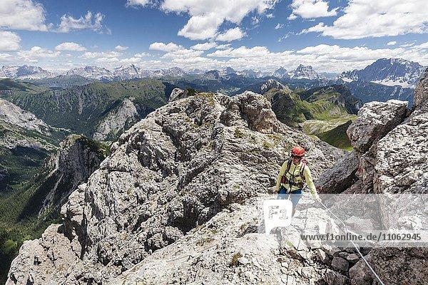 Mountaineer ascending to Cima d'Auta on the Via Ferrata Paolin Piccolin at Colmean  behind the Civetta and Pelmo  Falcade  Via Ferrata in Biois  Dolomites  Province of Belluno  Italy  Europe