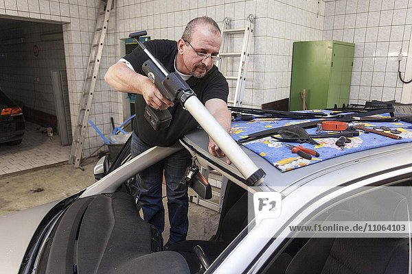 Changing the windscreen of a car in a garage for car glass  Düsseldorf  North Rhine-Westphalia  Germany  Europe