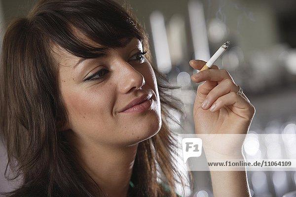 Junge Frau beim Rauchen in einer Bar oder Bistro  Deutschland  Europa