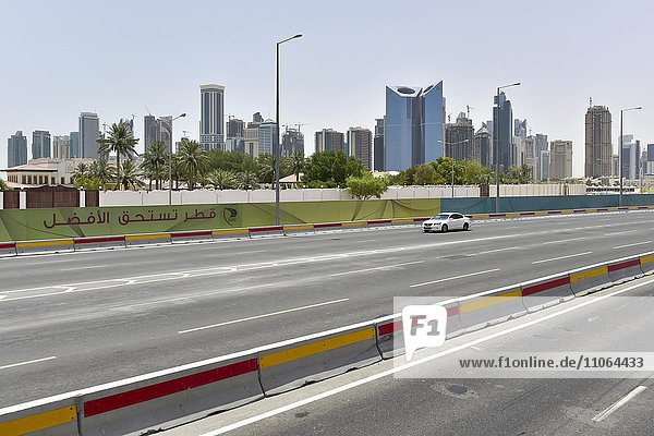 Car on a road with five lanes in front of the skyline of Doha  Qatar  Asia