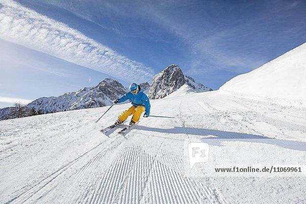 Skifahrer mit Helm fährt die Skipiste runter  Mutterer Alm bei Innsbruck  Tirol  Österreich  Europa
