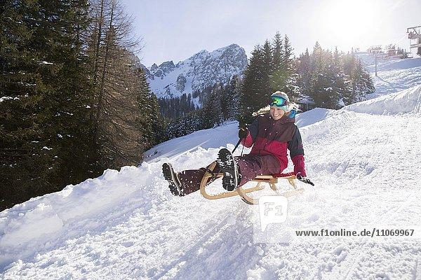 Junge Frau springt mit dem Rodel  Muttereralm bei Innsbruck  Tirol  Österreich  Europa