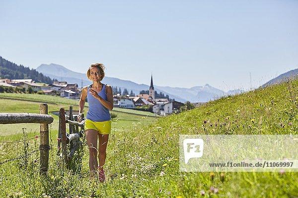 Frau joggt in einer Blumenwiese  Patsch  Rosengarten  Innsbruck  Tirol  Österreich  Europa Frau joggt in einer Blumenwiese, Patsch, Rosengarten, Innsbruck, Tirol, Österreich, Europa