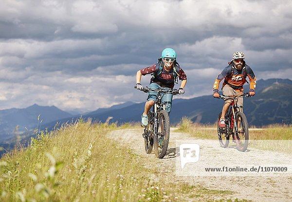 Zwei Mountainbiker mit Helm fahren auf einem Schotterweg  Mutterer Alm bei Innsbruck  Patscherkofel  Tirol  Österreich  Europa