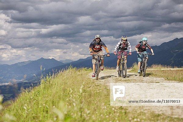 Drei Mountainbiker mit Helm fahren auf einem Schotterweg  Mutterer Alm bei Innsbruck  Tirol  Österreich  Europa