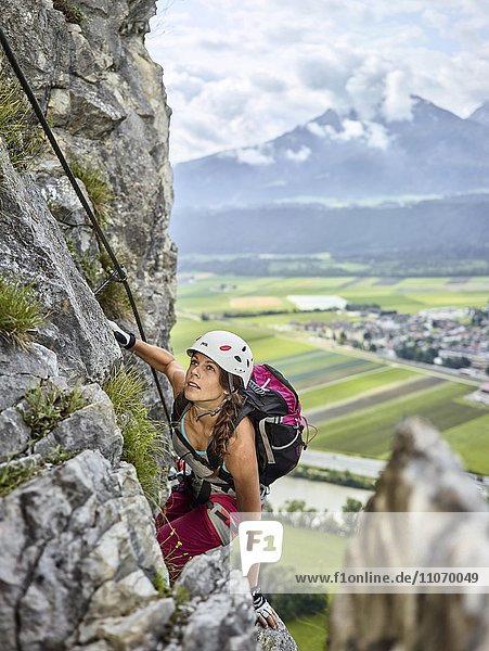 Bergsteigerin  Kletterin mit weißen Helm beim Aufstieg am Klettersteig  Zirl  Innsbruck  Tirol  Österreich  Europa