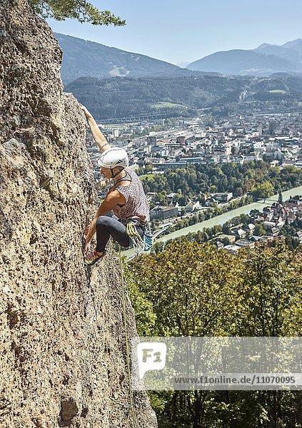 Female climber with helmet climbing on a rockface  Höttingersteinbruch  Innsbruck  Tyrol  Austria  Europe