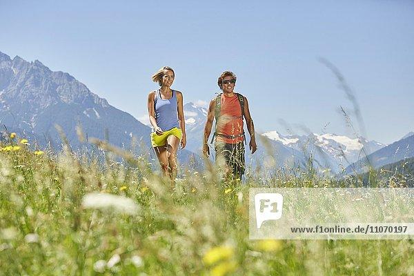 Mann und Frau wandern durch eine Wiese  Berge dahinter  von links Serles und Habicht und Stubaier Gletscher  Patsch  Rosengarten  Innsbruck  Österreich  Europa