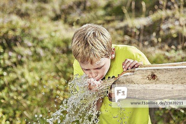Junge mit blonden Haaren trinkt Wasser von einem Brunnen  Hintertux  Zillertal  Tirol  Österreich  Europa