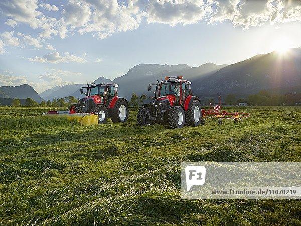 Zwei Traktoren mähen und verteilen das geschnittene Gras mit einem Heuwender  Kundl  Inntal  Tirol  Österreich  Europa
