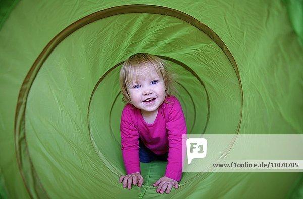 Kleines Mädchen mit rosa T-Shirt krabbelt durch grünen Spieltunnel  Deutschland  Europa