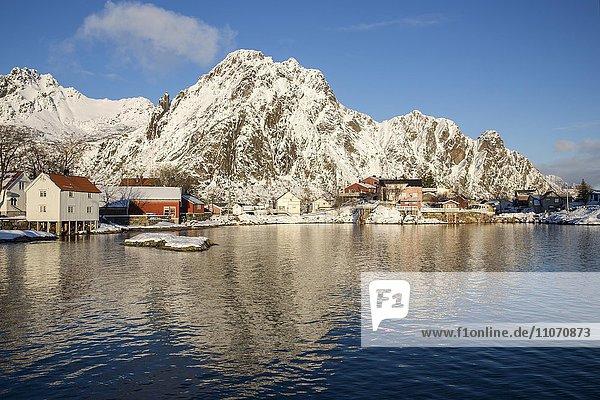 Wohnhäuser an der Hafeneinfahrt von Svolvær vor schneebedeckten Bergen  Svolvaer  Austvågøya  Lofoten  Nordland  Norwegen  Europa