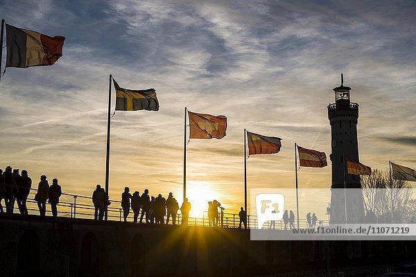Silhouetten von Menschen und Fahnen bei Sonnenuntergang  Hafen in Lindau am Bodensee  Bayern  Deutschland  Europa