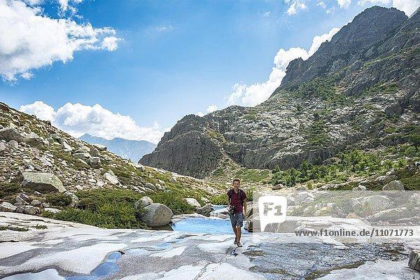 Junger Mann wandert am Fluss Golo im Gebirge  Regionaler Naturpark Korsika  Parc naturel régional de Corse  Korsika  Frankreich  Europa