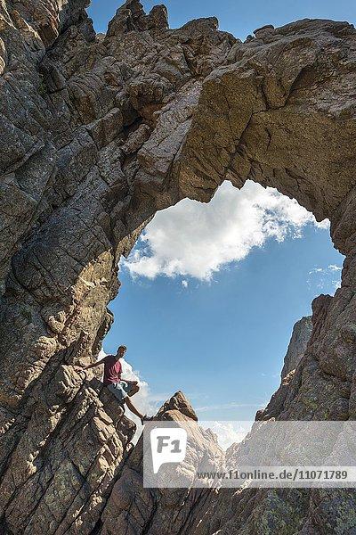 Junger Mann sitzt im Bombentrichter  Bombenloch  U Tafonu di u Compuleddu  Trou de la Bombe  Col de Bavella  Bavella-Massiv  Korsika  Frankreich  Europa