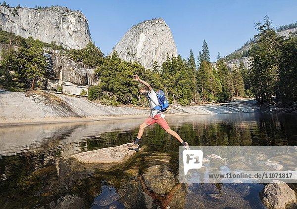 Junger Mann springt von Stein zu Stein  Fluss Merced River  Liberty Cap  Mist Trail  Yosemite-Nationalpark  Kalifornien  USA  Nordamerika