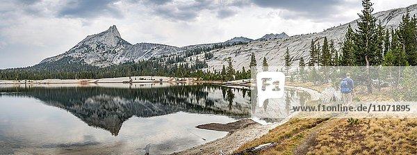 Junger Mann auf Wanderweg am See  Berg spiegelt sich in einem See  Cathedral Peak  Lower Cathedral Lake  Sierra Nevada  Yosemite Nationalpark  Cathedral Range  Kalifornien  USA  Nordamerika